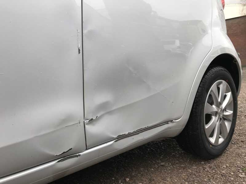 side of dented white vehicle